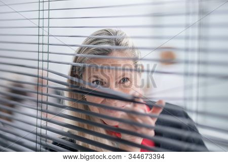 Smiling Businesswoman Looking Through Office Window Blinds