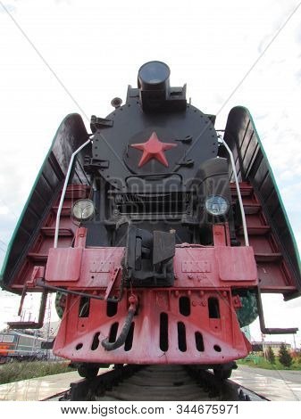 Black Steam Locomotive, With A Red Star On A White Background, As If Ready To Rush Forward To The Fu