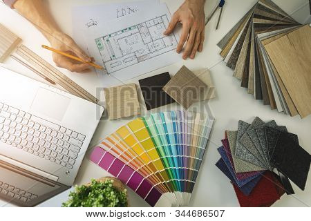 Designer Working In Office Doing Furniture And Flooring Material Selection From Samples For Home Int