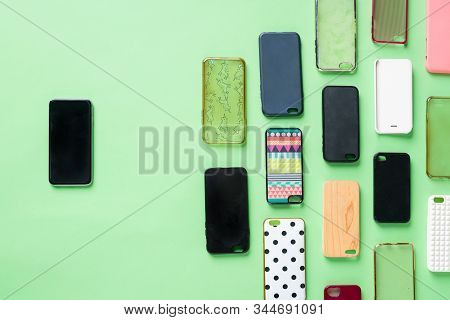 Pile Of Multicolored Plastic Back Covers For Mobile Phone On Green Background. Choice Of Smart Phone