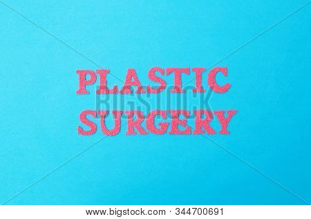 Inscription Plastic Surgery In Red Letters On A Blue Background. The Concept Of Procedures In Plasti