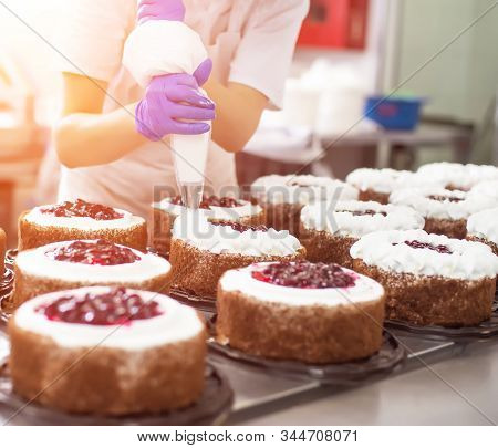Pastry Chef Girl Makes A Cake From Fresh Biscuit Berries And Cream. Mass Production Of Cakes And Swe