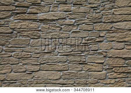 Beige-colored Decorative Stone Wall, Texture, Background. Tan Or Light-brown Stones Of Irregular Sha