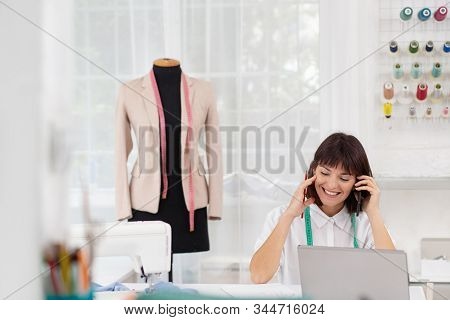 Young Female Dressmaker Working In Sewing Studio. Businesswoman Talking On The Phone With A Client.