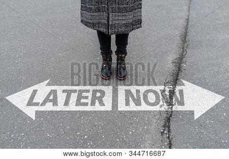 Legs Of Woman Standing Behind Arrow Road Marking With Text Now And Later, Call To Action And Procras