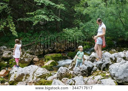 Mother With Children Having Fun, Playing By A Mountain Creek In Summer. Outdoor Lifestyle, Positive