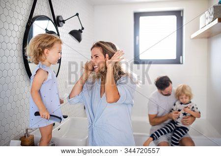 Young Family With Two Small Children Indoors In Bathroom, Having Fun.