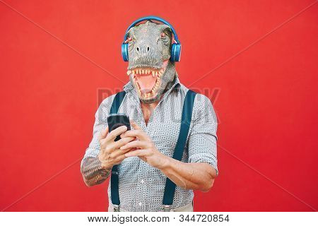 Senior fashion man wearing t-rex mask using mobile smartphone listening music with headphones - Crazy bizarre hipster guy having fun with new technology - Funny and absurd surreal concepts