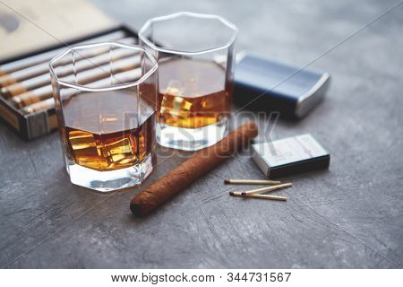 Carafe of Whiskey or brandy, glasses and box of finnest Cuban cigars on an gray stone table. With ice cubes