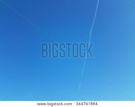 Moon And Contrail Or Cloud In Blue Sky