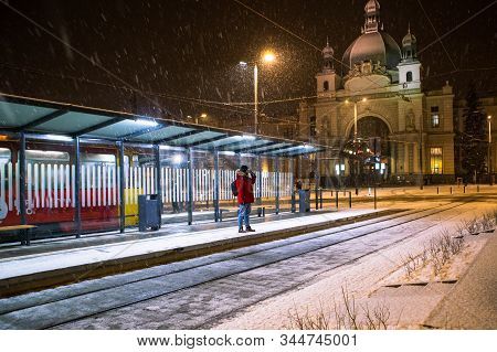 Man In Red Winter Coat Standing At Bus Tram Stop Waiting For Public Transport