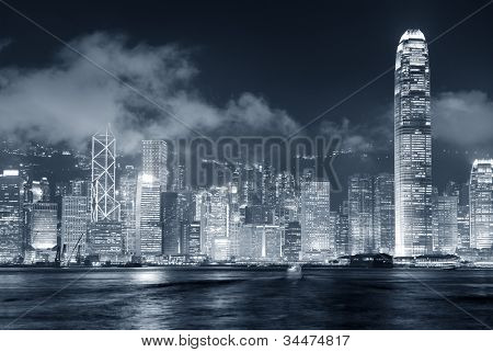Hong Kong skyline at night with clouds over Victoria Harbour in black and white.