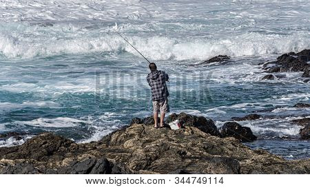A fisherman casting his fishing rod into the water at the atlantic ocean. saltwater fishing, Tenerife, Canary Islands, Spain