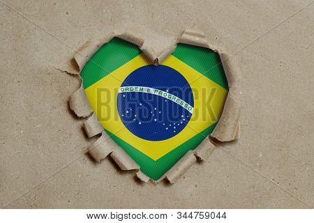 3d illustration. Heart shaped hole torn through paper, showing Brazilian flag