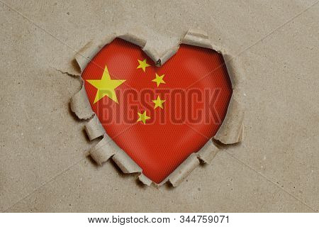 3d illustration. Heart shaped hole torn through paper, showing Chinese flag