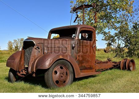 The Rusty Remnants Of An Old Unidentifiable Tow Truck With Missing Wheels Is Full Of Rust And Corros