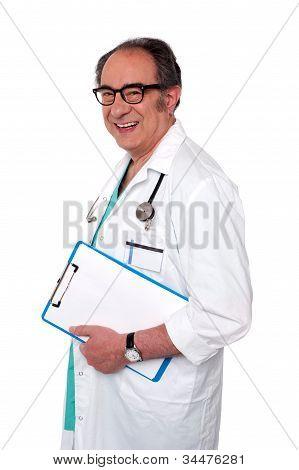 Senior Male Doctor Holding Blank Clipboard