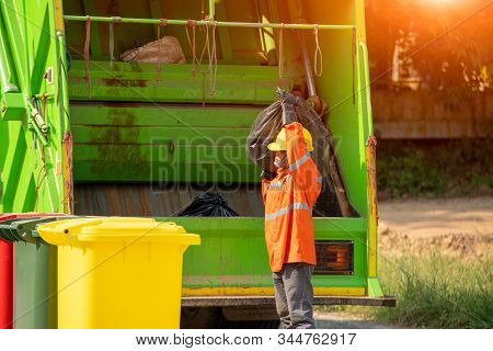 Garbage Collection Worker Putting Bin Into Waste Truck For Removal With Truck Loading Waste.