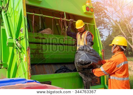 Two Garbage Men Working Together On Emptying Dustbins For Trash Removal With Truck Loading Waste And