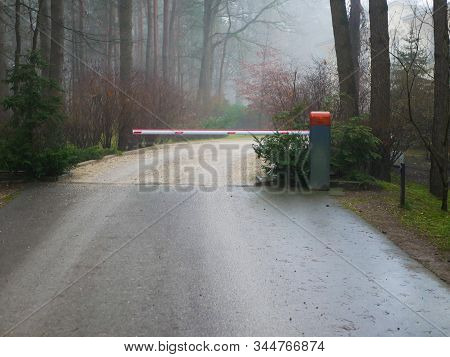 Closed Forest Barrier. Country Road In The Forest With A Closed Red White Barrier. The Protection Of