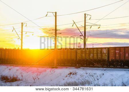 Karelia, Russia - January, 12, 2020: A freight train crosses a railway bridge over the Kem River in Karelia, Russia, at sunset in winter