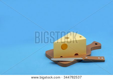 Paper Triangular Piece Of Maasdam Cheese With Large Holes On Cutting Board. Dairy Products Made From