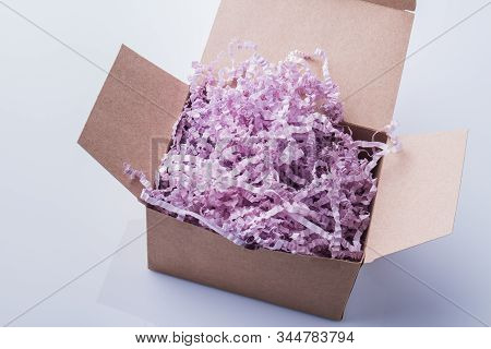 Cardboard Box Overfilled With Shredded Paper. White Isolated Background.