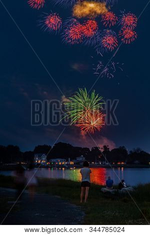 NORWALK, CONNECTICUT, USA - JULY3, 2015. Fireworks with people celebrating 4th of July seen in Norwalk Veterans park