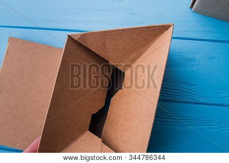 Uncovering Carton Cardboard Box, Close-up. Top View. Blue Wooden Surface Background.