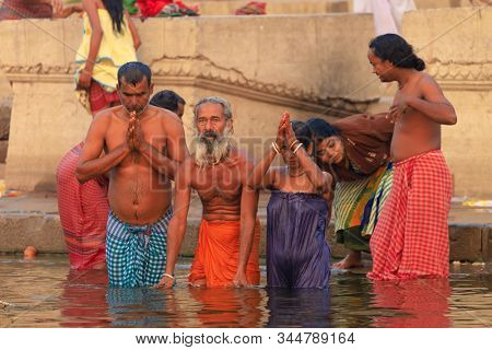 VARANASI, INDIA, JANUARY 18, 2019 : A family is bathing at sunrise along the Varanasi Ghats, traditional Hindu ritual.