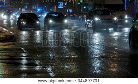 Cars Driving In The Night City Street After Heavy Rain