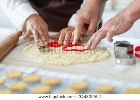 Close Up Senior Couple Hands Making Cookies With Red Cutters In Heart Shape.