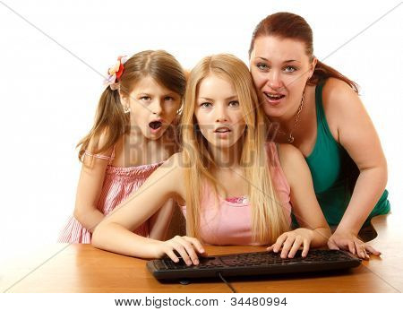 mother with daughters looking with interest in monitor, isolated on white