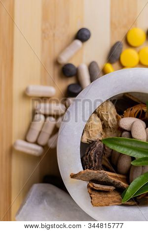 Portrait Shot Of Ayurvedic Tablets And Capsules In A Mortar Against Brown Wooden Background. Ayurved