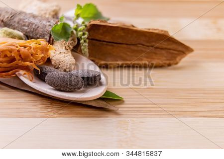 Three Black Ayurvedic Tablets With Ocimum Sanctum Leaves And Dry Spices Against A Wooden Background.