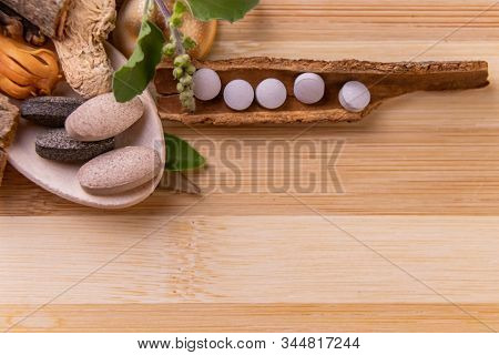 White Herbal Tablets Arranged Horizontally On A Wooden Bark With Whole Spices And Green Herbs. Herba