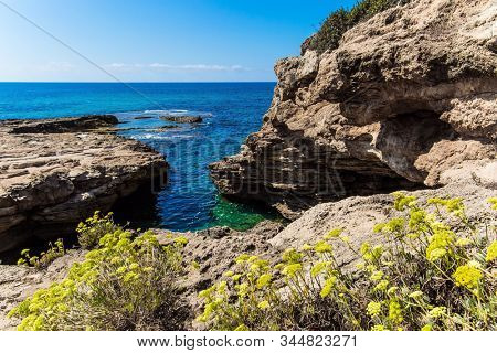 Rocky bay near chalk mountain Rosh a Nikra - geological formation in northern Israel. The color of sea water changes from azure to dark blue. The concept of active, eco and photo tourism