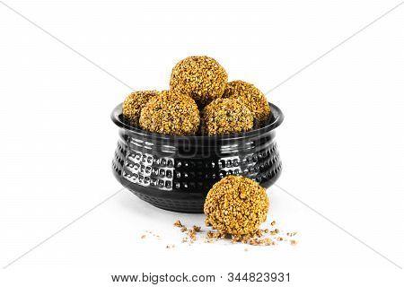 Sesame Seed Ball Or Tilgul Laddo In Black Bowl Isolated On White Background. Indian Festival Makar S