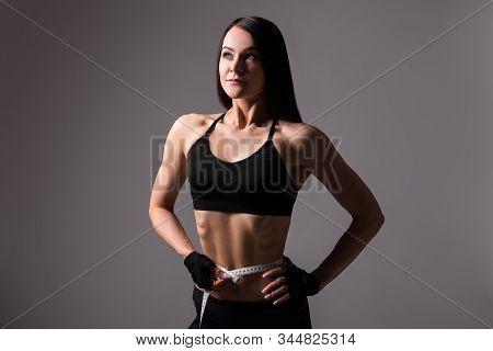 Portrait Of Young Beautiful Sporty Woman With Muscular Body Measuring Waistline Over Gray Background