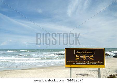 Caution Sign On White Sand Beach