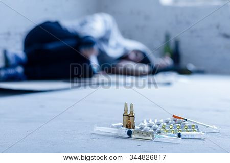 Closeup Syringes, Ampoules And Pills. On Background Young Junkie Homeless Addict Man Is Sleeping Aft
