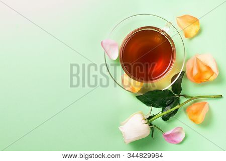 Cup Of Morning Tea And Roses On A Green Background..rose Petals.