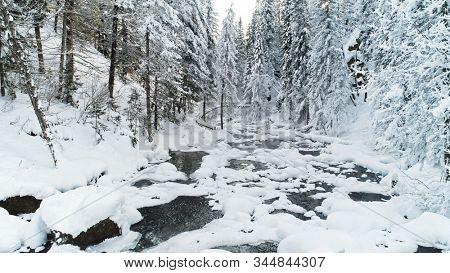 Small river in the winter forest covered snow. Russia, Siberia, Altai region
