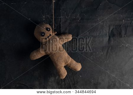Voodoo Doll On A Black Background With Dramatic Lighting. The Concept Of Witchcraft And Black Art An