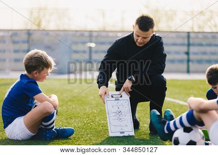 Young Soccer Trainer Coach Explaining Tactic On Team Sports Tactics Board. Children During Soccer Fo