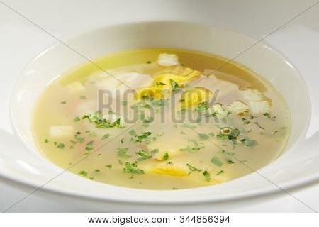Chicken bouillon with tortellini pasta in white restaurant bowl isolated. Homemade noodle soup, clear sturdy seasoned broth with yellow egg spaghetti and greens closeup