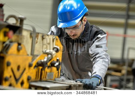 Young apprentice using steelworks machine