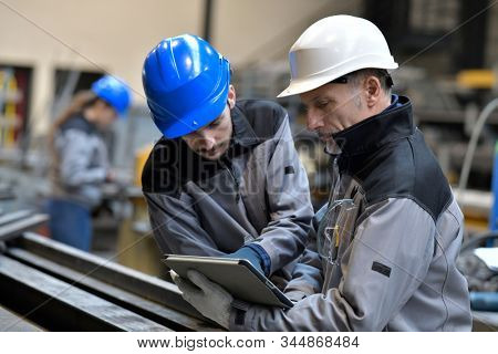 Apprentice working in steelworks plant, with instructor