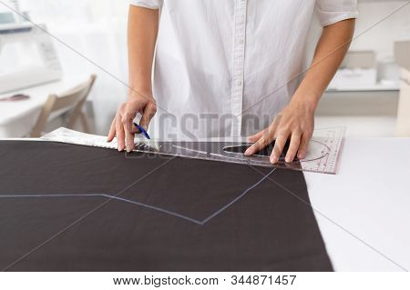 Young Female Dressmaker Making A Pattern On A Piece Of Dark Cloth. Close Up Portrait Of Fashion Desi