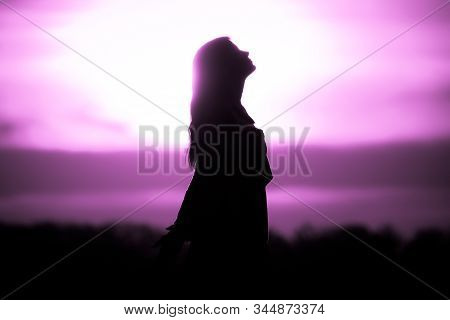 Youth Woman Soul At Pink Sun Meditation Awaiting Future Times. Silhouette In Front Of Sunset Or Sunr